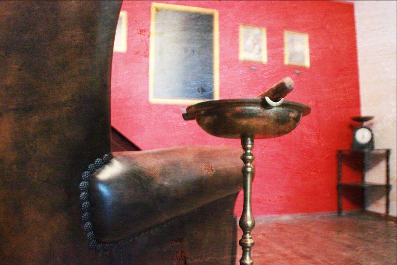 Bild aus dem Escape Room Codename Eagle bei Think² in Bochum: Ein Sessel, ein Aschenbecher und eine rote Wand mit mehreren Gemälden.