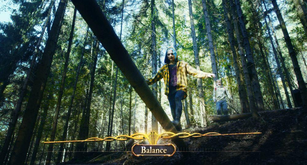 Ein Mädchen mit blauen Haaren balanciert über einen Baumstamm im Wald.