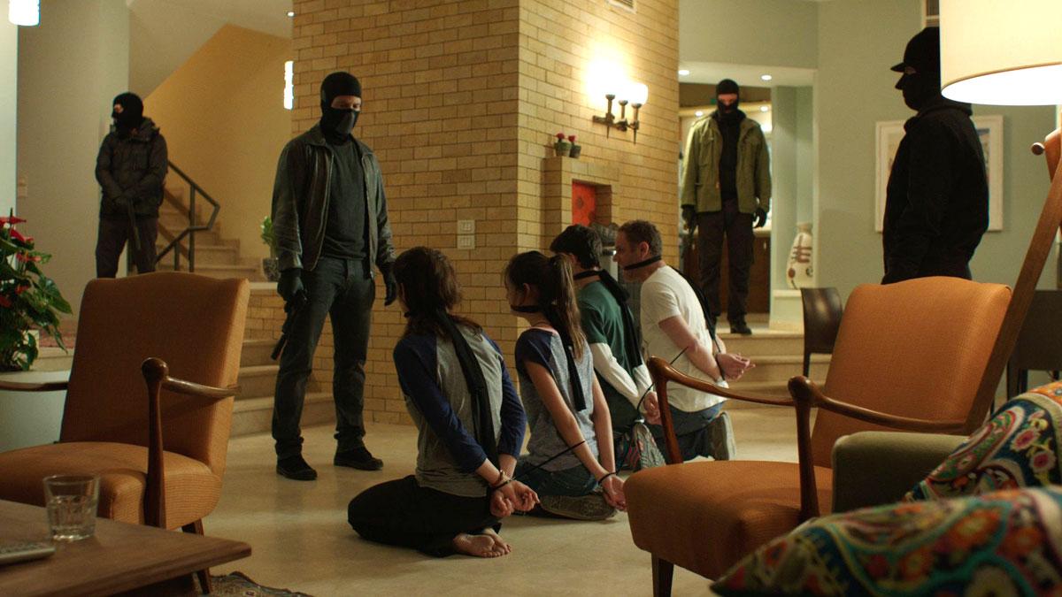 Filmszene aus die Geiseln: Eine Familie kniet gefesselt und geknebelt in einem Wohnzimmer, umgeben von maskierten Männern.