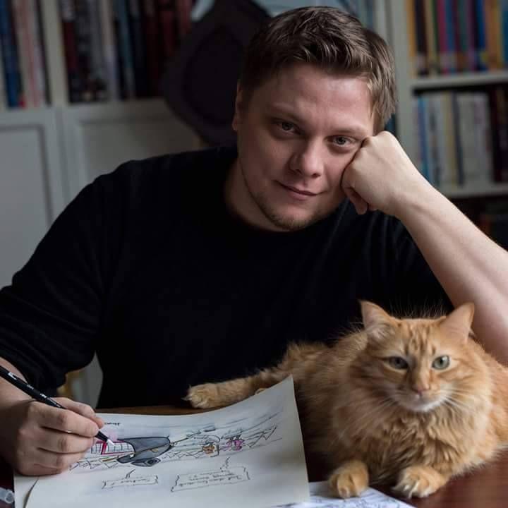 Michael Holtschulte mit Zeichenblatt, Tod-Cartoon und Katze.