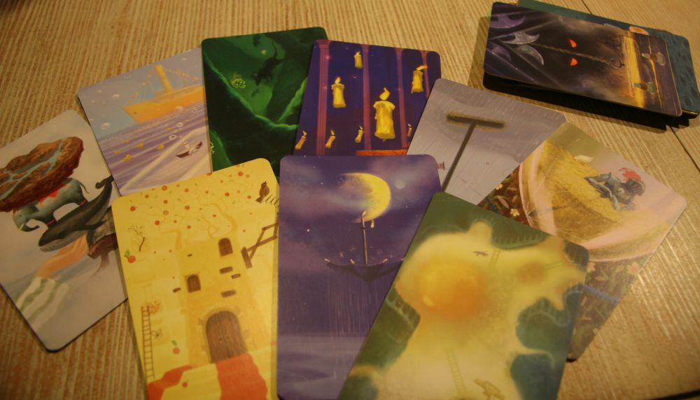 die visionskarten von mysterium zeigen surreale bilder wie einen regenschirm in der mondsichel hängend, schwebende kerzen oder einen elefanten auf dem rücken eines wales stehen.