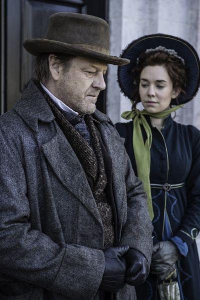 Szene aus Frankenstein Chronicles: Ein Mann in Hut und Mantel neben einer Frau mit Haube und Halstuch.