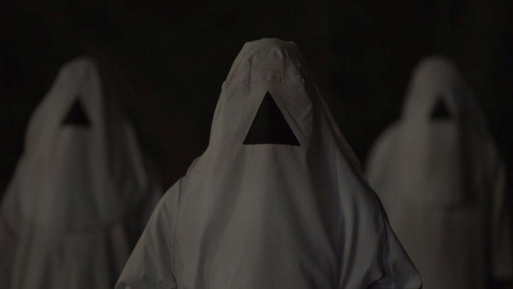 Gestalten in weißen Kutten, mitten im Gesicht ist ein schwarzes Dreieck auf dem Stoff.
