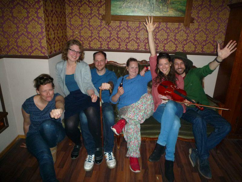 sechs fröhliche menschen auf einer couch posieren mit scherlock holmes utensilien nach bestehen von escape berlin