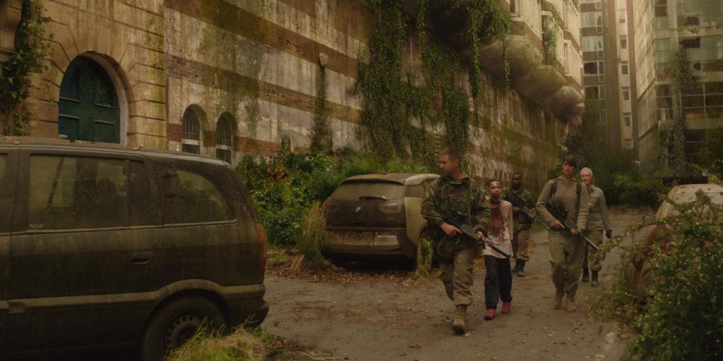 Szene aus the girl with all the gifts: Bewaffnete Menschen bewegen sich durch von Pflanzen überwucherte Straßen.