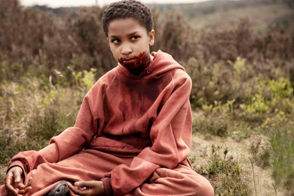 Ein Mädchen in einem roten Overall mit blutverschmiertem Mund.