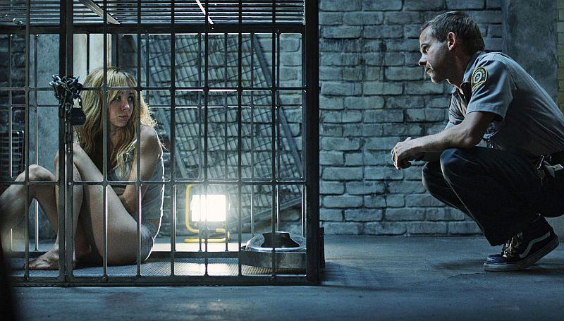 Szene aus Pet: Wenn du etwas liebst, dann lass es nicht los. Eine spärlich bekleidete Frau in einem Stahlkäfig, davor kniend ein Mann in einer Uniform.