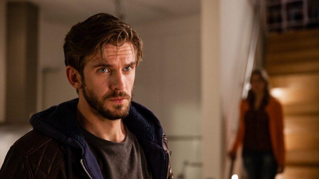 Szene aus Kill Switch: Ein Mann mit Bart steht in einem Hausflur, hinter ihm ist undeutlich eine Frau zu erkennen, die eine Treppe heruntergeht.