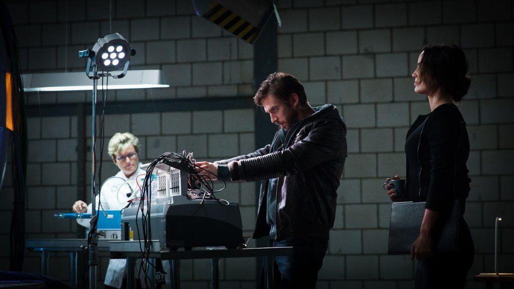 Ein Mann untersucht ein mit vielen Kabeln versehenes Gerät. Links und rechts von ihm steht jeweils eine Frau und sieht ihm zu.