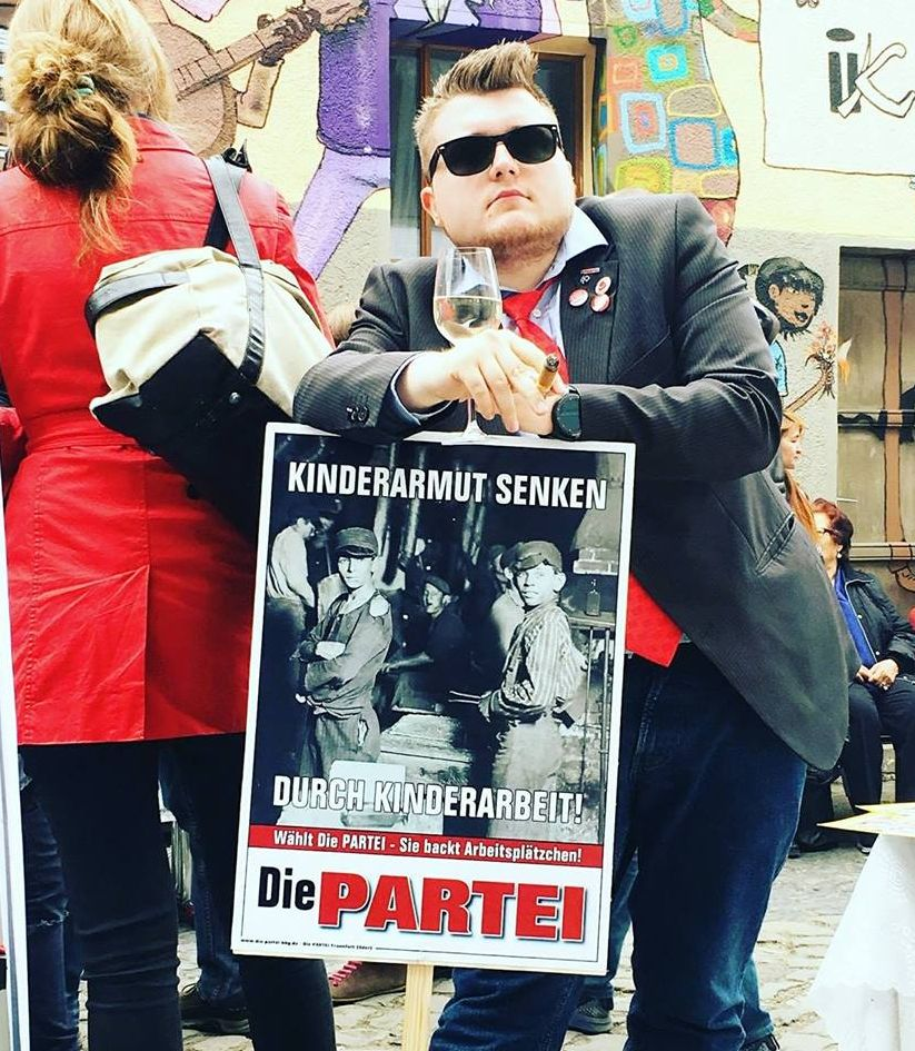 """Julian Klippert - ein Mann im Anzug mit Sonnenbrille, Zigarre, Weinglas und dem Plakat """"Kinderarmut senken durch Kinderarbeit die Partei"""" Auf dem Plakat sind Kinderarbeiter auf einer alten Fotografie abgebildet."""
