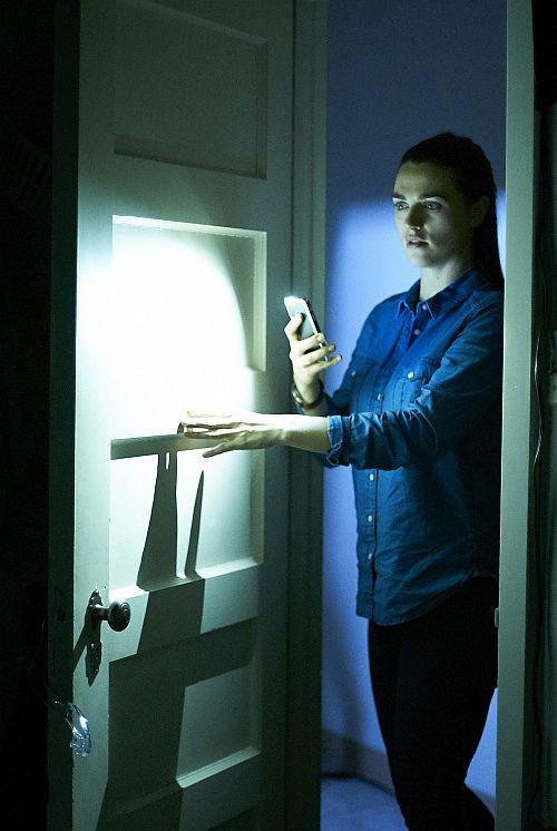 Eine Frau hält ein Handy in der Hand, während sie eine Tür öffnet.