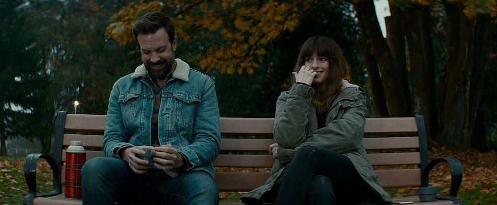 Ein Mann und eine Frau sitzen auf einer Parkbank, beide lachen.