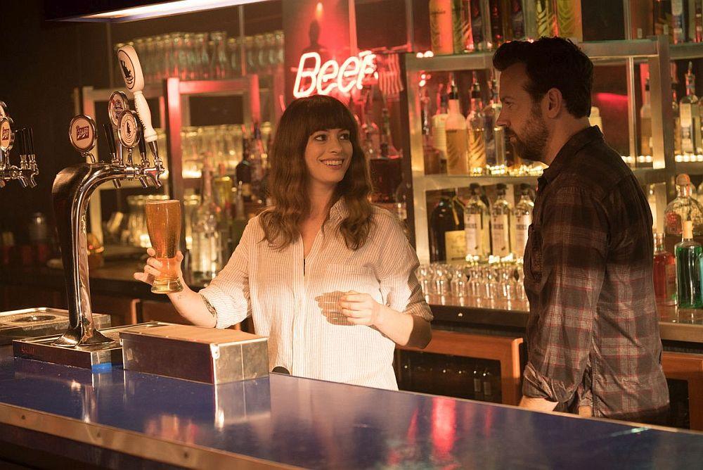 Eine Frau zapft ein Bier an einer Bar und lächelt einen Mann neben sich an.