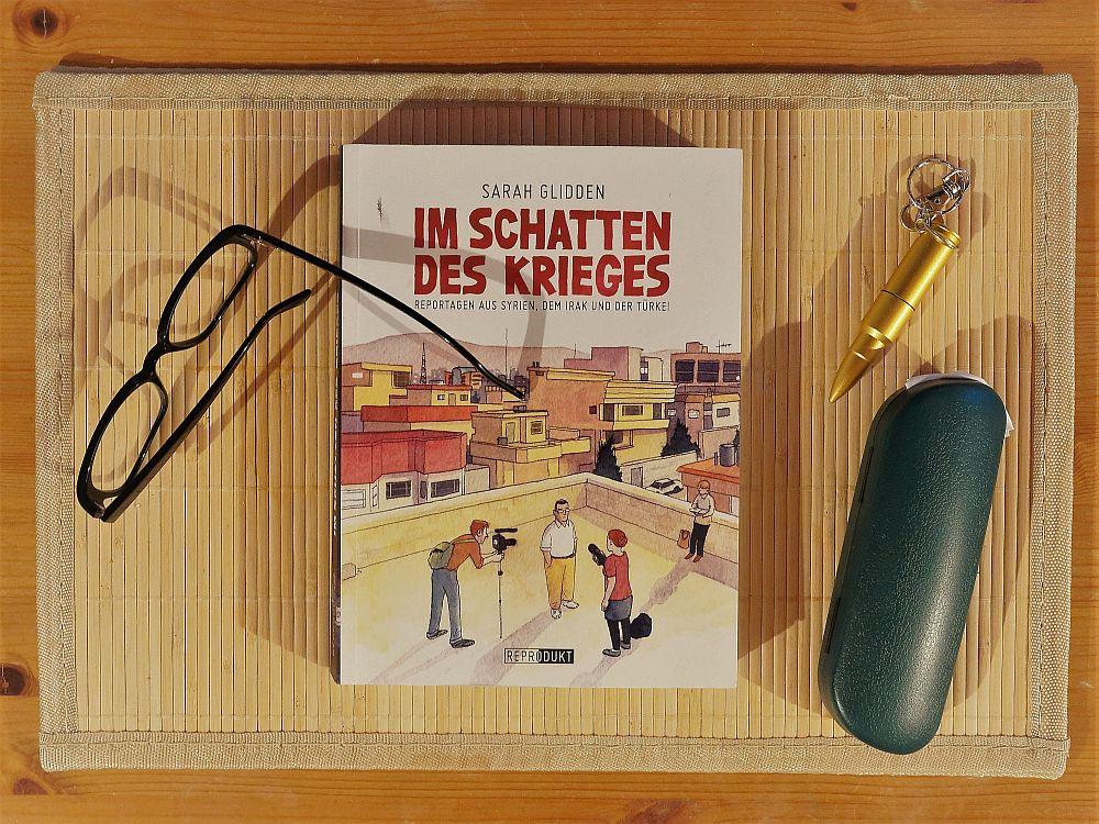 Der Comicband Im Schatten des Krieges auf einem Tisch neben einer Brille, einer Patrone und einem Brillenetui.