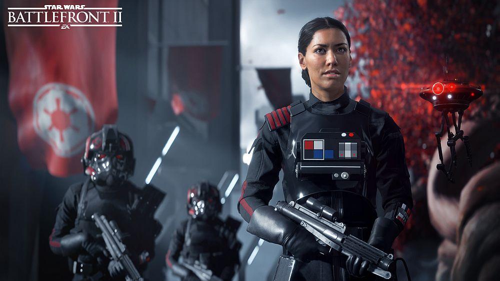 Eine Frau mit einem Blaster in imperialer Star Wars-Uniform, hinter ihr weitere Menschen in schwarzer Rüstung vor dem Banner des Imperiums.
