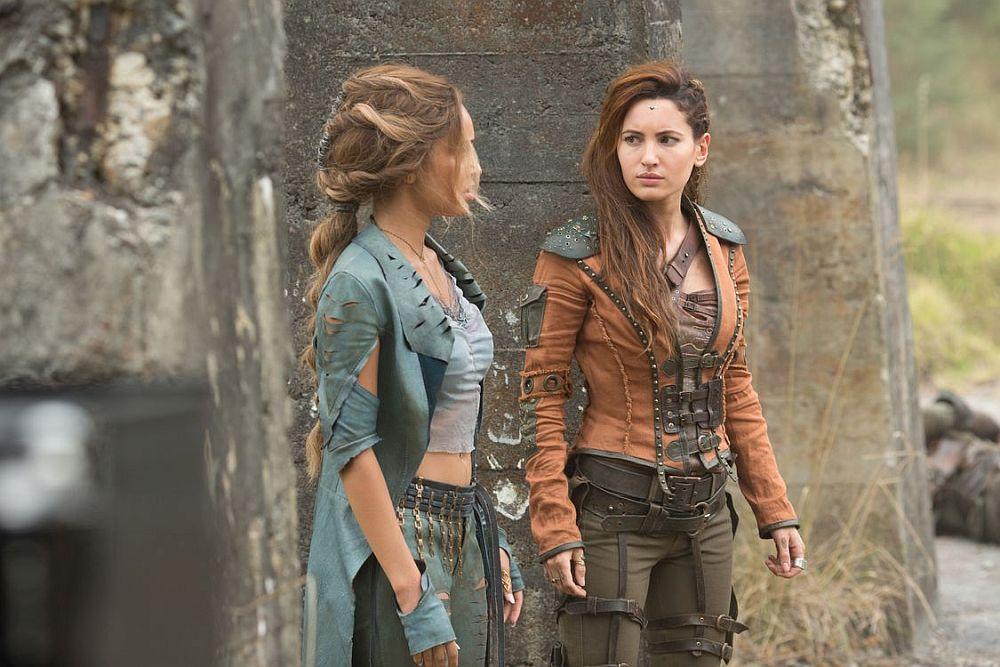 Zwei Frauen in altertümlich wirkender aber funktionaler Kleidung stehen vor einer Betonmauer