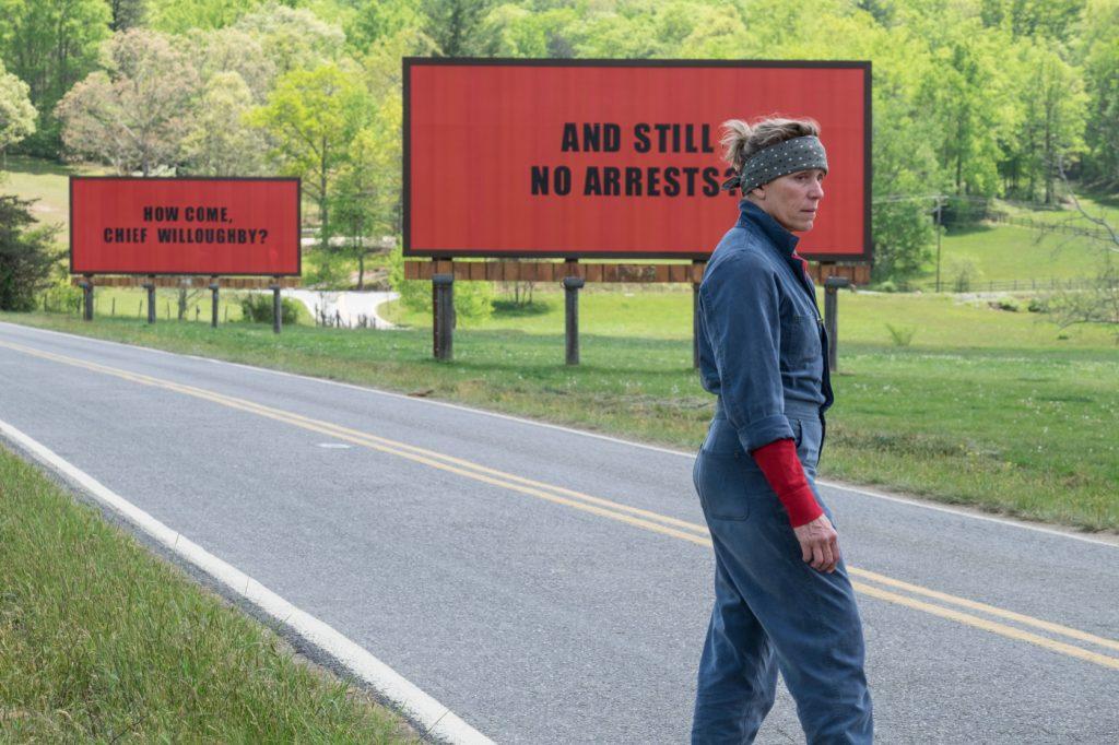 Eine Frau an einer Landstraße vor zwei Werbetafeln, auf denen How come Chief Willoughby? und And still no arrests? steht.