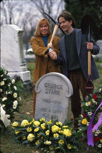 Ein Mann und eine Frau reichen sich an einem Grabstein die Hände. Auf dem Grabstein steht George Stark.