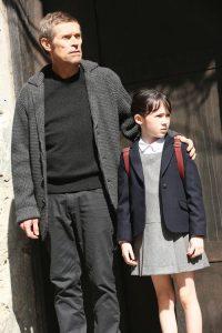 Ein älterer Mann in Strickjacke und ein kleines Mädchen in Schuluniform.