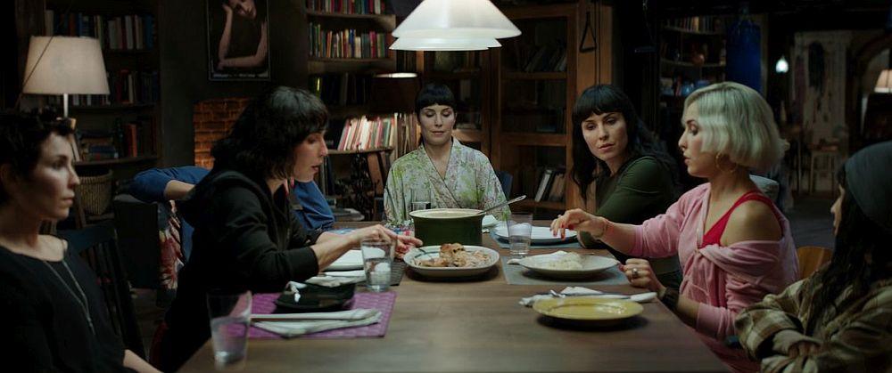 Sieben gleich aussehende Frauen in unterschiedlichen Outfits an einem Tisch.