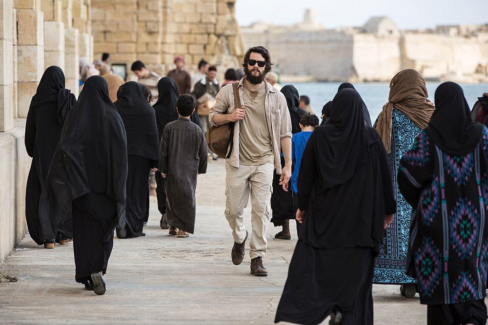 Ein bärtiger Mann mit Sonnenbrille an einem Hafen, um ihn herum viele verschleierte Frauen.