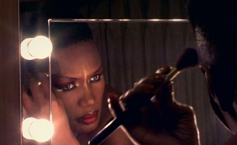 Grace Jones schminkt sich vor einem Spiegel.