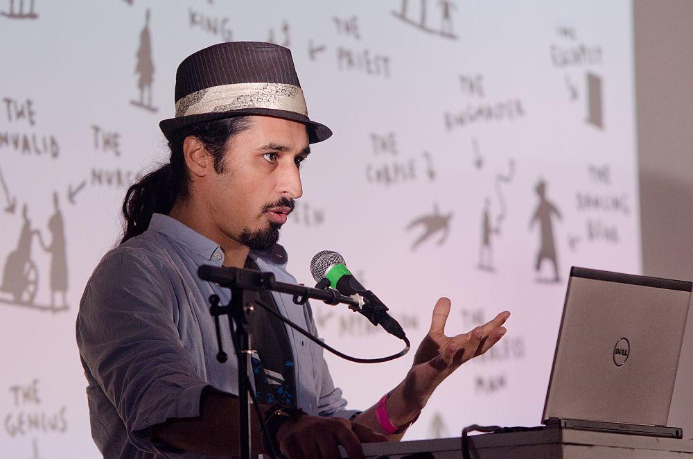 Ein Mann mit Hut und Kinnbart spricht in ein Mikrophon.
