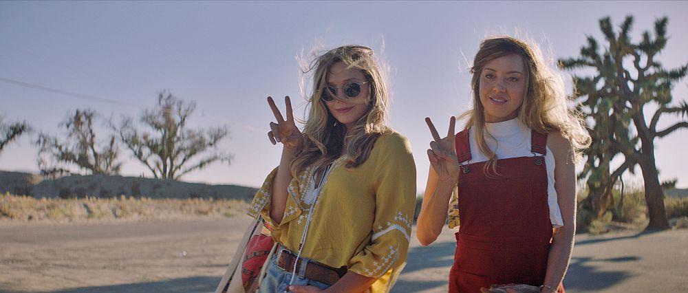 Zwei Frauen in hipper Kleidung posieren mit zum Peace-Zeichen gehobenen Fingern.