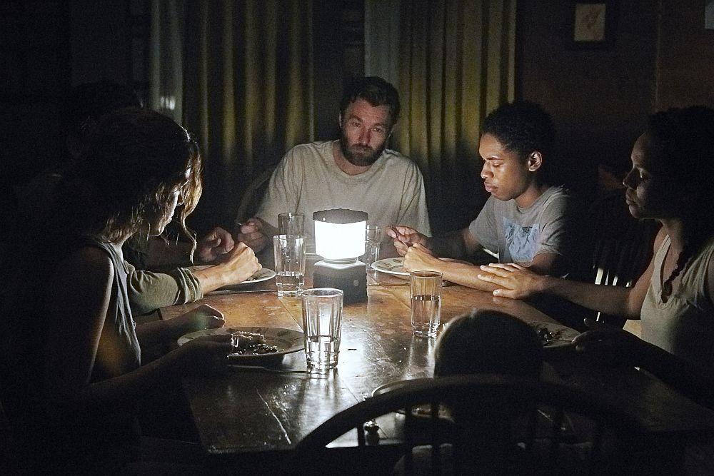Eine Gruppe von Menschen sitzt im Dunkeln an einem Tisch, nur von einer Campinglaterne beleuchtet.