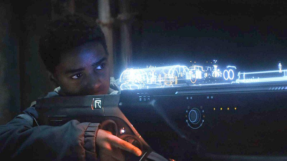 Ein Junge zielt mit einer futuristischen Laserwaffe