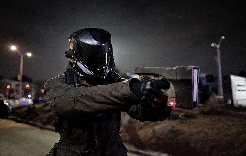 Eine Gestalt mit Helm zielt mit einer futuristischen Waffe