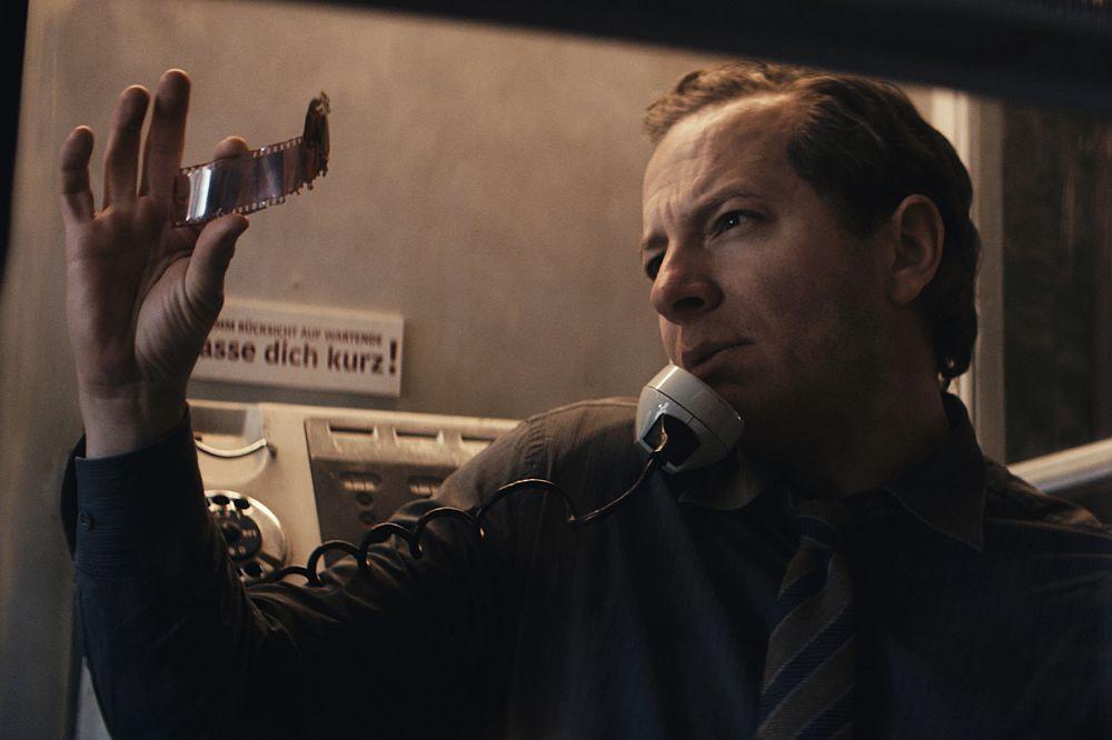 Ein Mann steht in einer Telefonzelle und betrachtet einen Streifen Filmnegative.