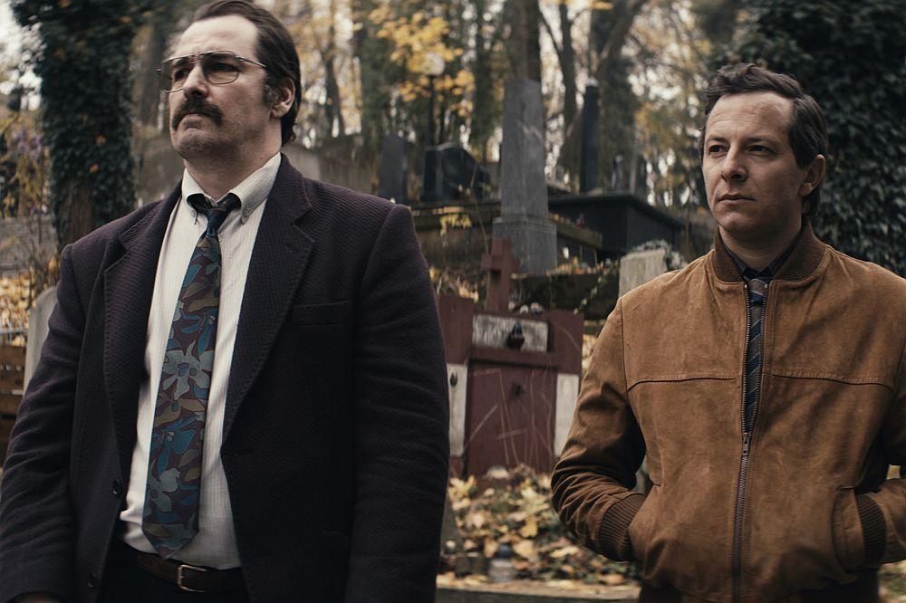 Zwei Männer stehen auf einem Friedhof.