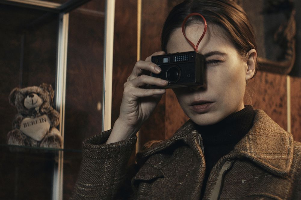 Eine Frau schaut durch das Objektiv eines Fotoaparates. Hinter ihr ist ein kleiner Teddybär mit der Aufschrift Berlin zu sehen.