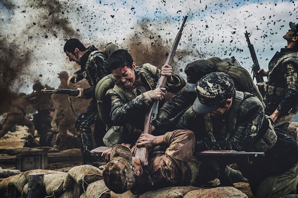 Mitten in einer Schlacht, drei Soldaten zwingen einen vierten in einer anderen Uniform nieder, während im Hintergrund durch Pulverdampf weitere Soldaten vorstürmen.
