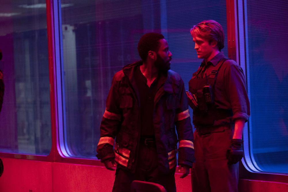 Zwei Männer im roten Licht. Hinter ihnen Fenster, der Raum dort ist in blaues Licht getaucht.