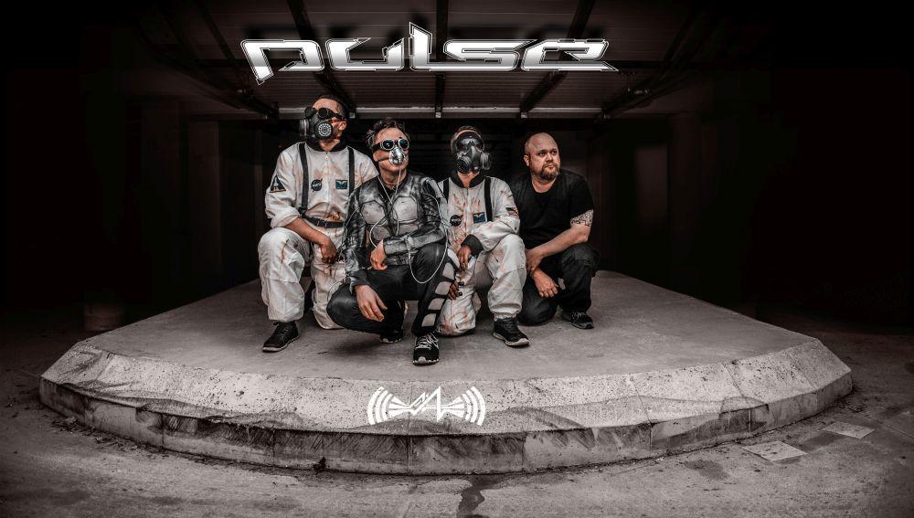 Bandfoto von Pulse: Vier Männer in Overalls, teilweise mit Atemmasken, knien auf einem Betonsockel.