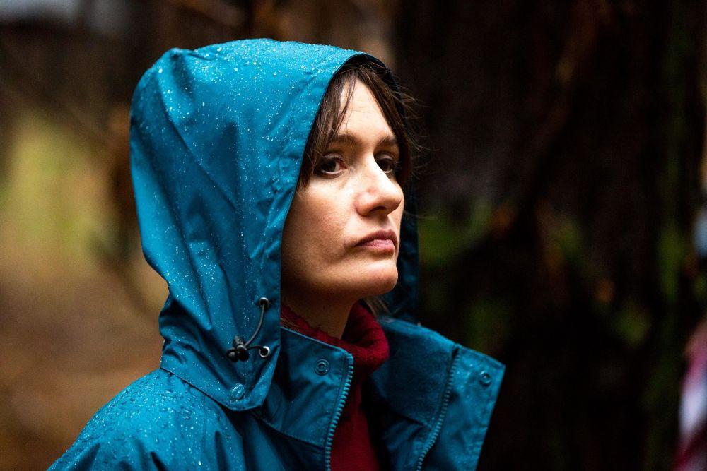 Eine Frau in Regenjacke mit Kapuze über dem Kopf steht im Wald.