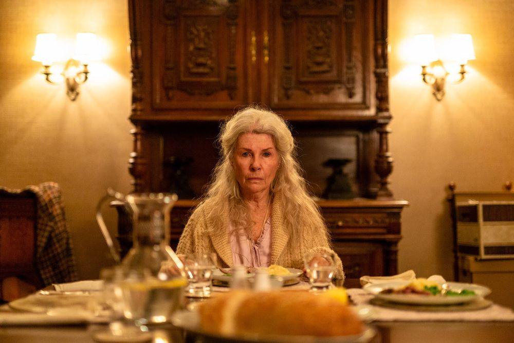 Eine alte Frau sitzt an einem gedeckten Tisch und schaut mit leerem Blick in die Kamera.