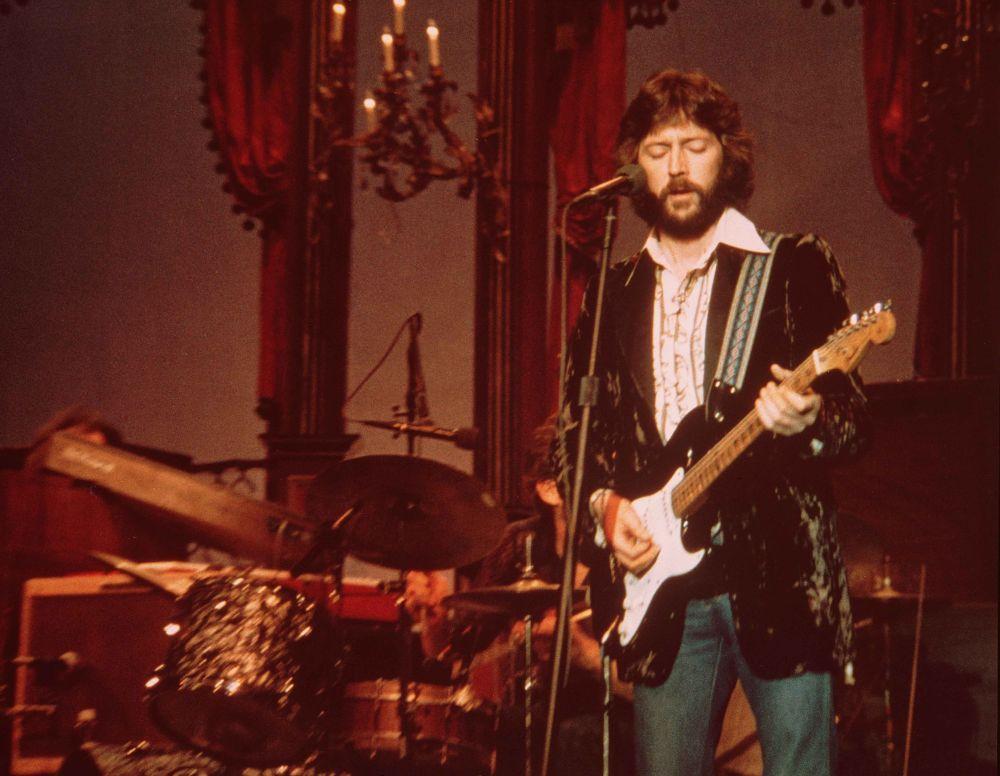 Ein Mann mit Vollbart spielt Gitarre auf einer Bühne.