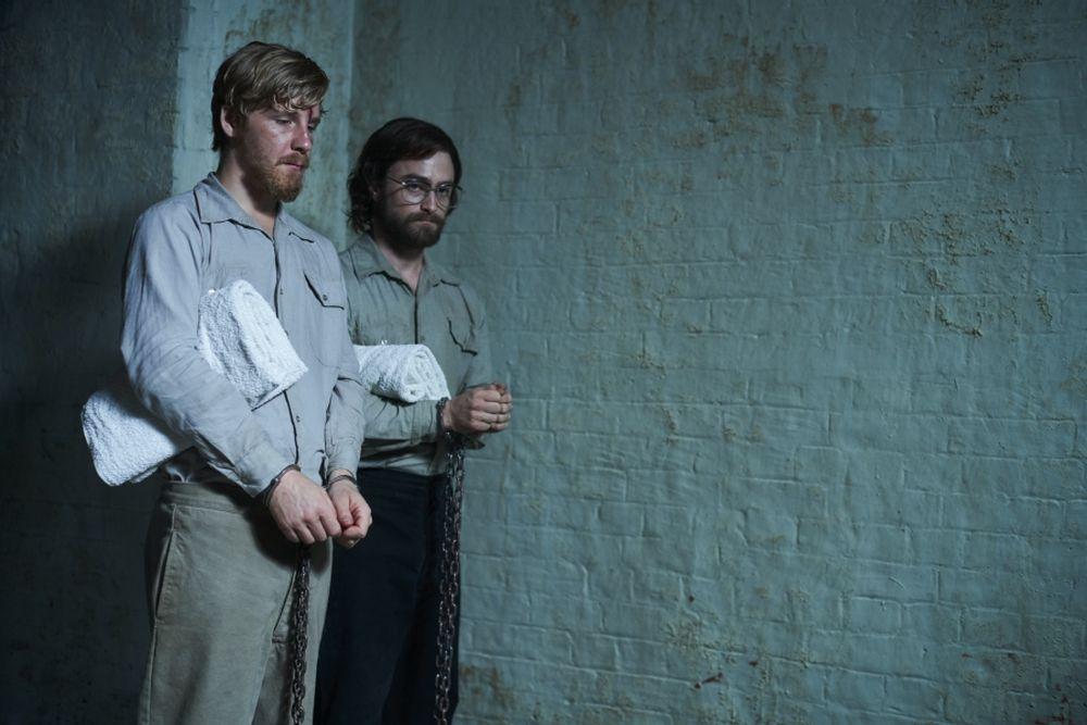 Zwei bärtige Männer mit Handfesseln stehen in der Ecke einer Gefängniszelle. Sie sehen niedergeschlagen aus.