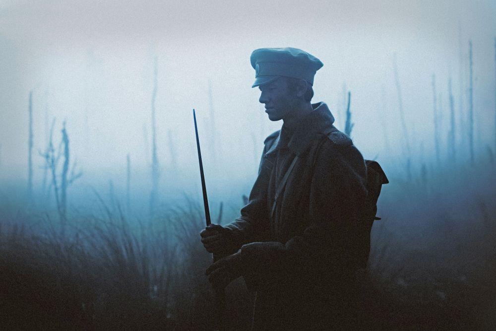 Ein Soldat pflanzt im Nebel sein Bajonett auf.