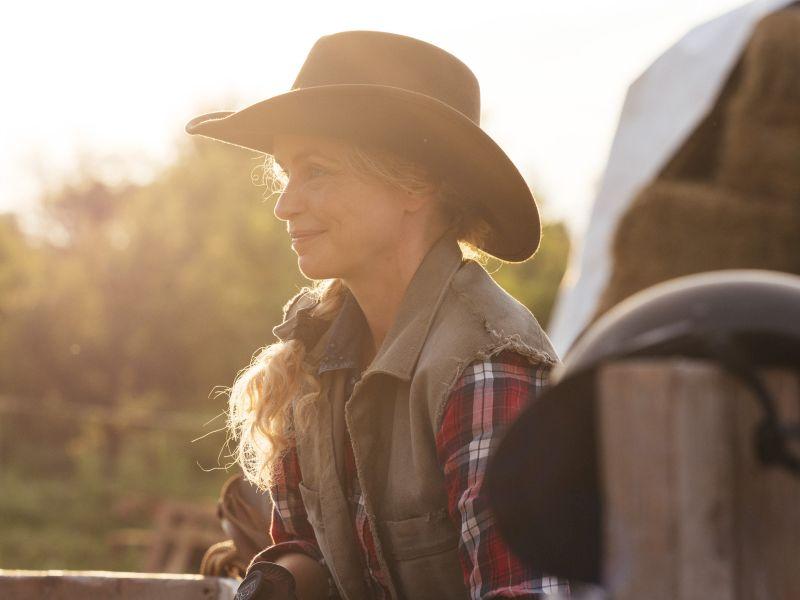 Eine blonde Frau mit Cowboyhut steht lächelnd an einem Zaun.
