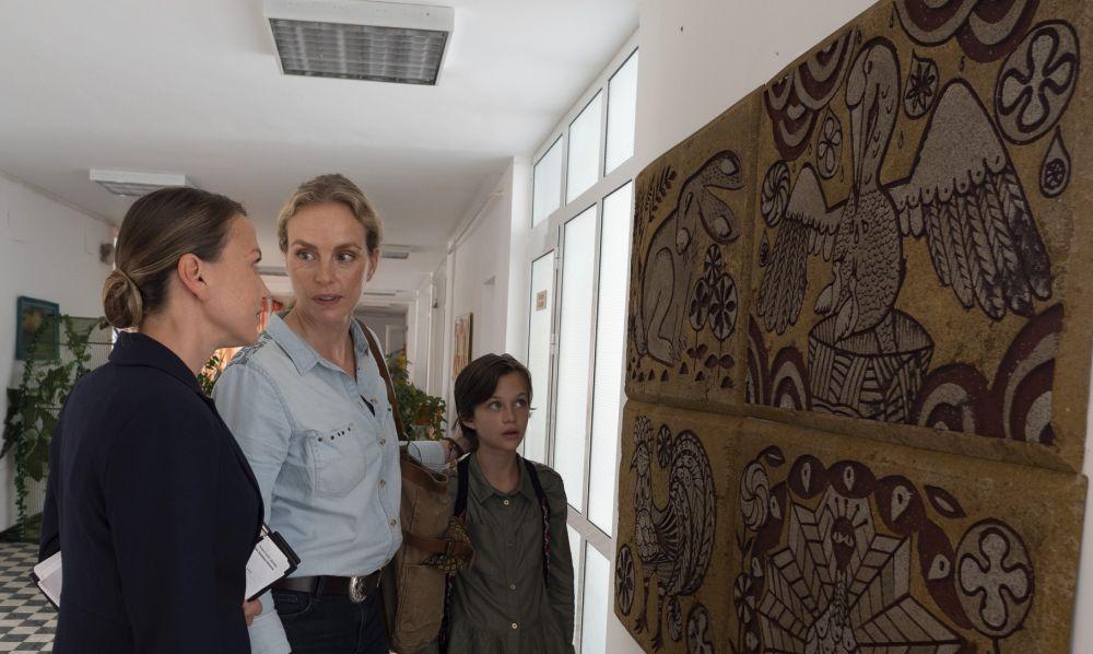 Ein Mädchen und zwei Frauen vor einem Wandgemälde, das zeigt, wie eine Pelikanmutter sich an der Brust verletzt, um ihre Jungen zu füttern.