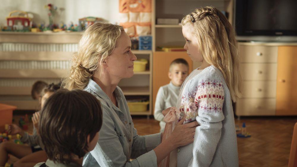 Eine blonde Frau schaut einem blonden Mädchen in die Augen.
