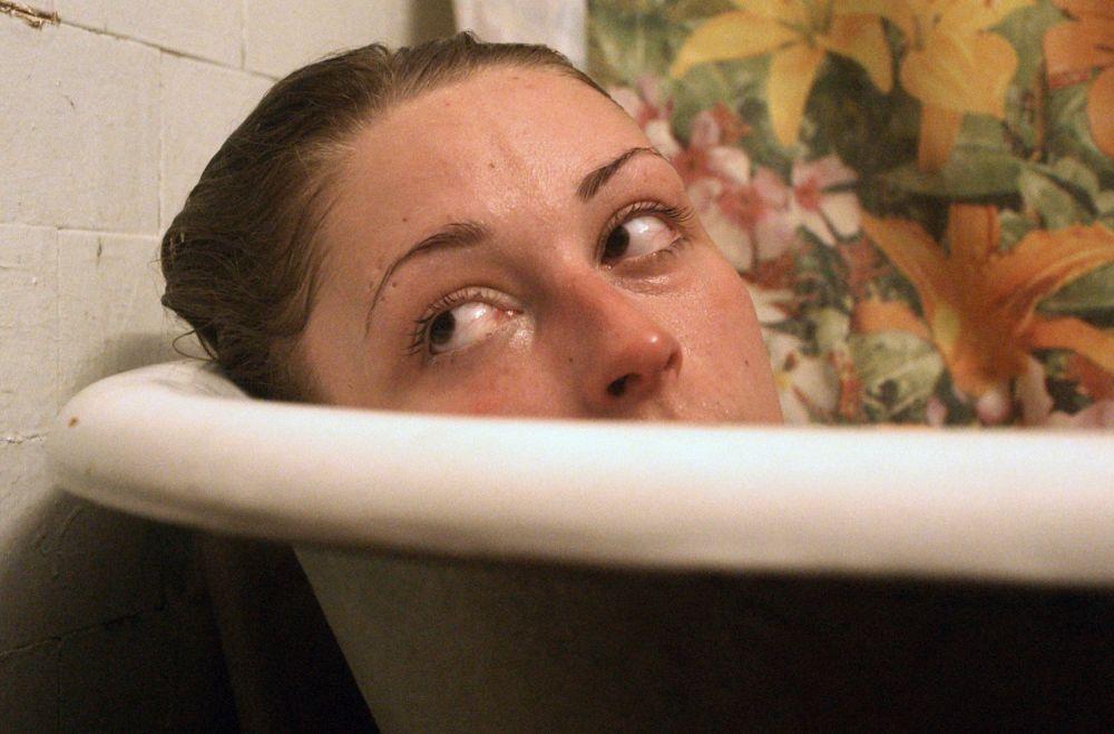 Das Gesicht einer Frau ragt halb aus einer Badewanne.
