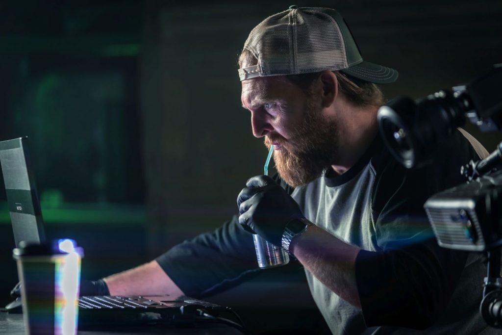 Ein bärtiger Mann mit Baseballkappe schaut auf einen Monitor