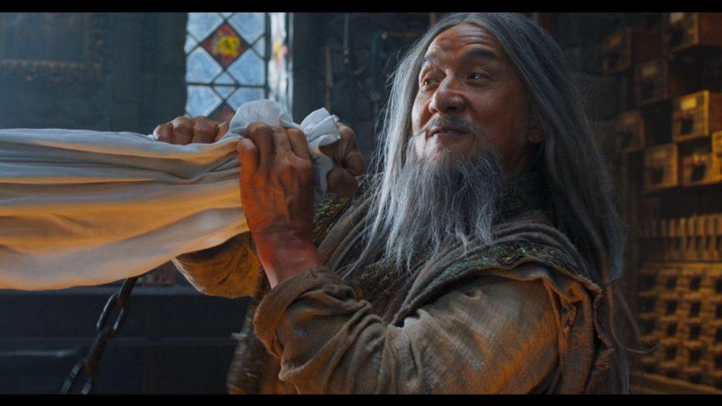 Ein Mann mit langem Bart und langen Haaren hält ein Tuch mit beiden Händen fest.