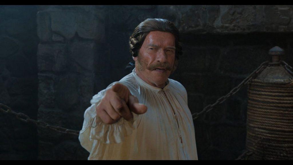 Ein Mann mit Perücke und Schnauzer zeigt mit dem Finger Richtung Kamera.