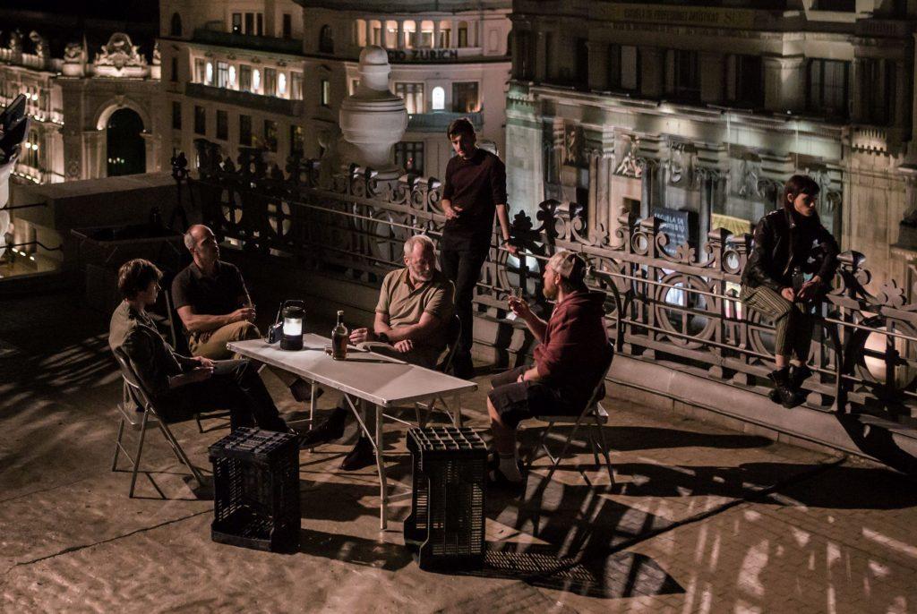 Sechs Leute auf einem Hausdach in Madrid. Einige sitzen an einem Tisch und trinken.